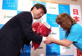 花束を受け取り、笑顔で握手する古賀友一郎さん(左)=21日午後8時45分、長崎市茂里町、県医師会館