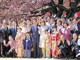 今年4月の「桜を見る会」で招待客と記念写真に納まる安倍首相と妻の昭恵氏=東京都新宿区の新宿御苑で