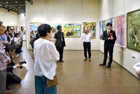 公募の部・県美展賞の作品について解説する堀之内聖さん(右)=鹿児島市の黎明館