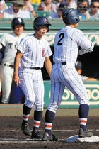 一塁コーチャーを務める浦和学院・阿部選手(手前左)