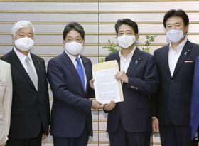 ミサイル防衛に関する検討チームの提言を安倍首相に手渡す小野寺元防衛相(中央左)=4日午後、首相官邸