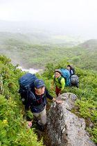 荒々しい岩場を登る一行。眼下に眺望が開けた時間もあった=西川町