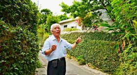車も通れない狭い路地に立つ壺屋町民会自治会長の島袋文雄さん。「壺屋は民家と民家の距離が近く宿泊施設には向かない」と話す=那覇市壺屋