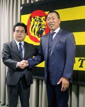 阪神の打撃コーチ就任が決まり、写真に納まる井上一樹氏(右)=21日、兵庫県西宮市