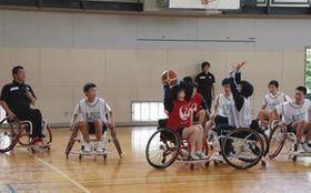 神保康広さん(左)のアドバイスを受けながら車いすバスケの試合をする生徒たち=氷見市西部中で