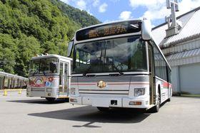 立山黒部アルペンルートの関電トンネルで来春から運行される電気バス。奥は現在運行中のトロリーバス=23日午前、長野県大町市