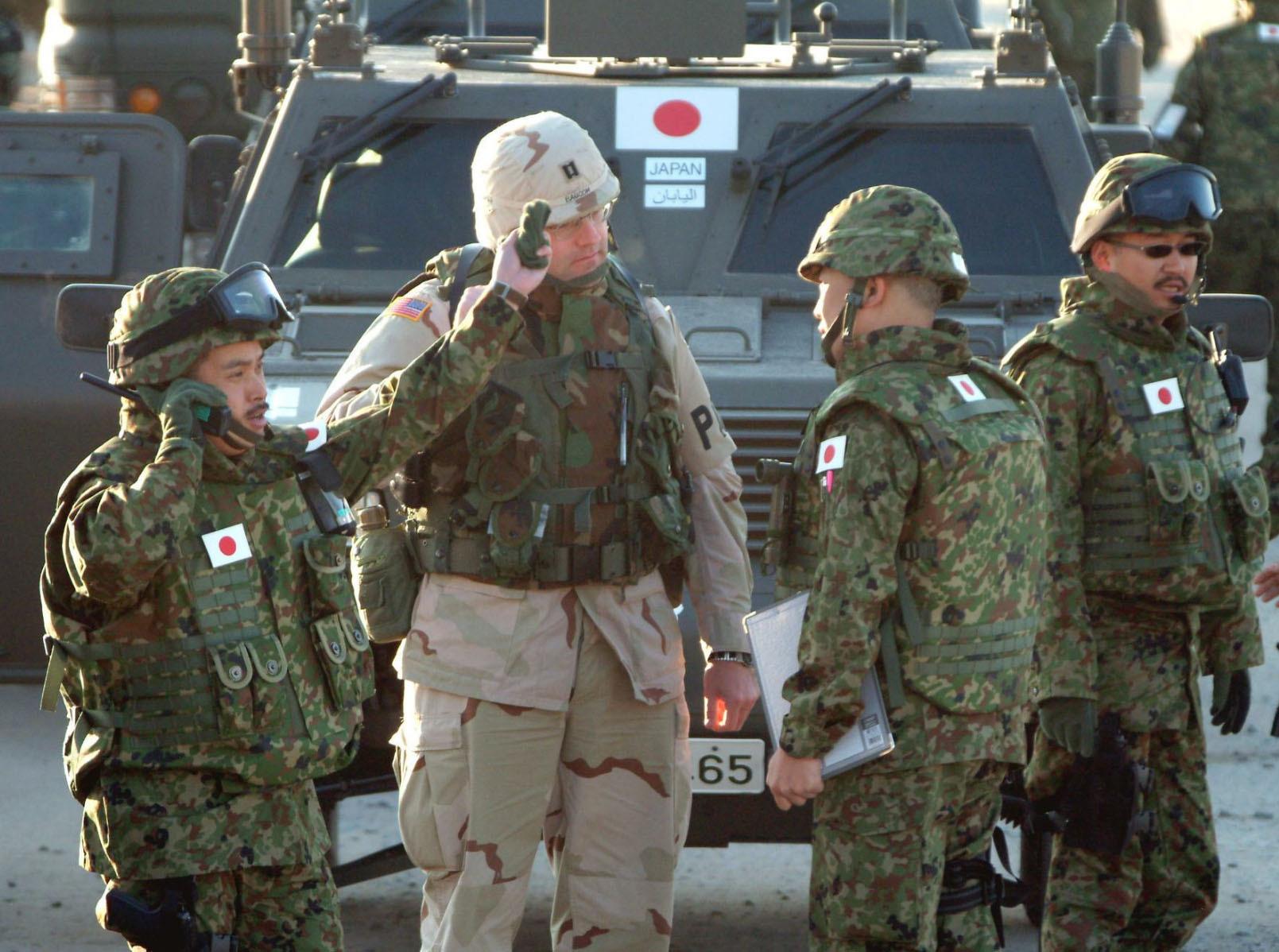 2004年2月、イラクとの国境付近の米軍キャンプで、米兵と打ち合わせする陸上自衛隊員=クウェート(共同)