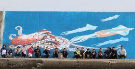 防波堤にケンサキイカとマダコの壁画を完成させた児童ら=平戸市、生月漁港