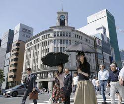 強い日差しの中、日傘を差して歩く人たち=23日午後、東京・銀座