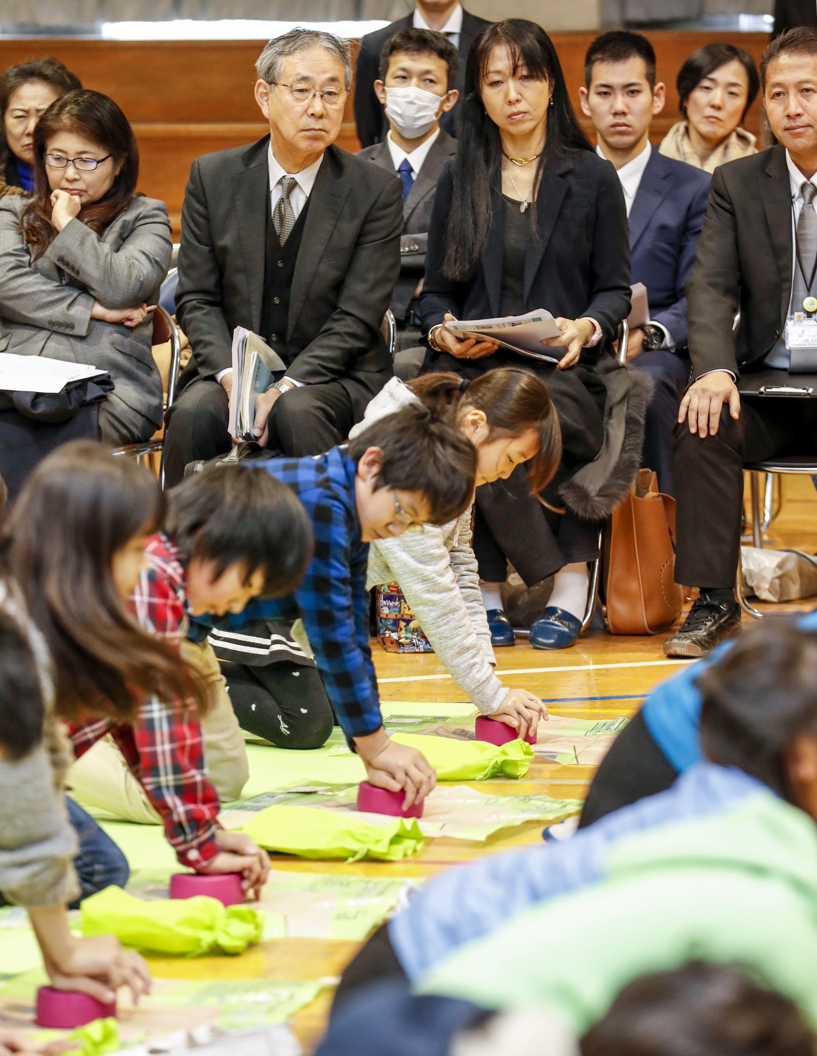 茨城県つくば市の小学校で、救命救急の講習を受ける児童を見守る桐田寿子(中央右)と桐淵博(同左)