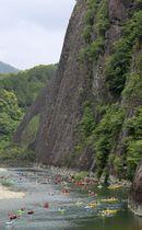 和歌山県古座川町で行われた、カヌーでごみを拾うクリーンアップ大作戦。後方は「一枚岩」=19日