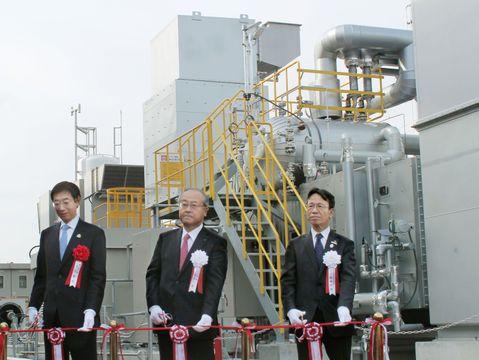 完成した水素発電施設の前で、テープカットをする久元喜造神戸市長(左)ら=10日、神戸市