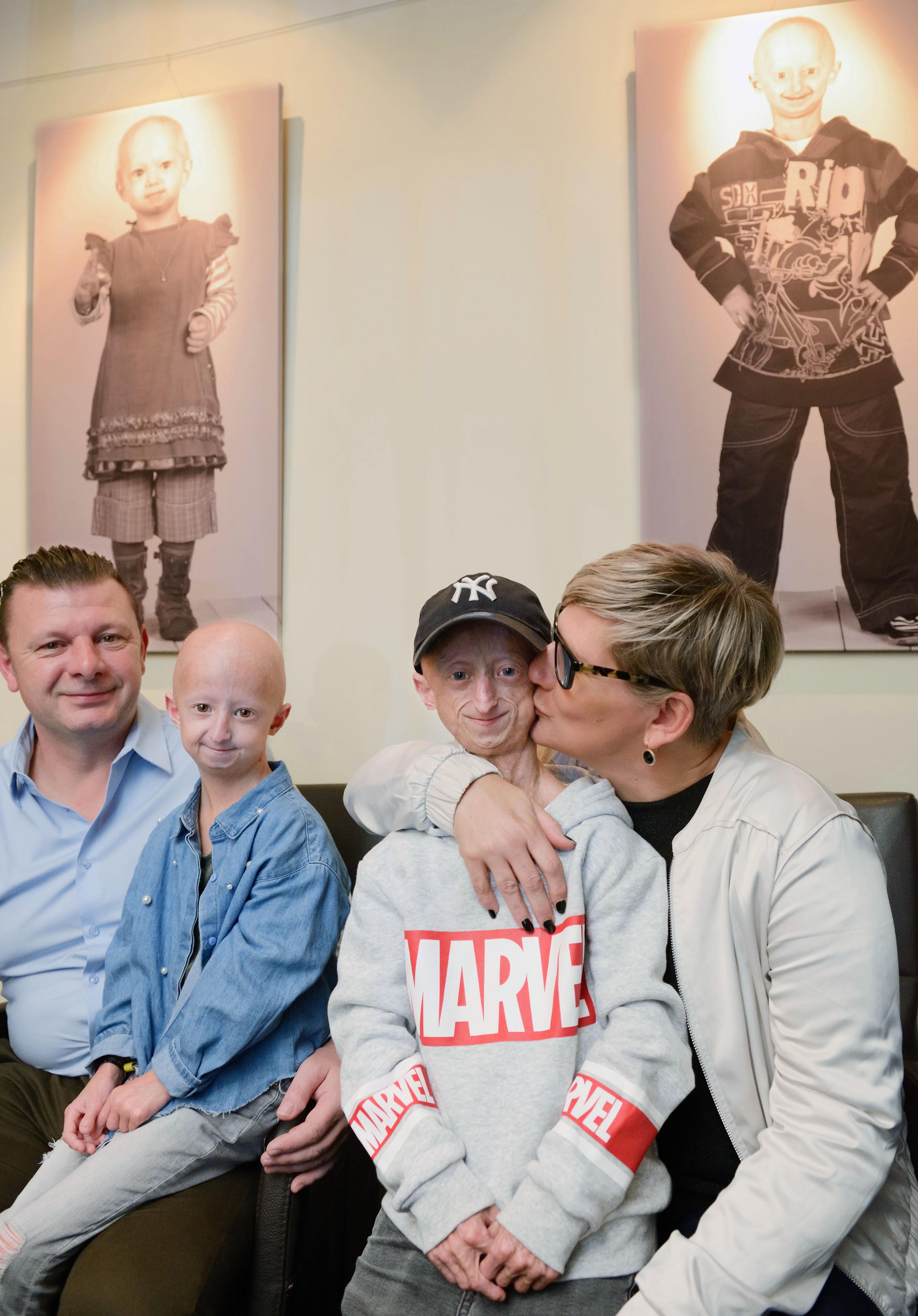 早老症を患う兄ミヒル・ファンデウェールト(中央右)と妹アンバー(同左)。父ウィムと母ホデリーベは、短くても充実した人生をと願う。家の中には子どもたちの生をいとおしむように何枚もの写真が飾られていた=ベルギー・ディーペンベーク(撮影・澤田博之、共同)