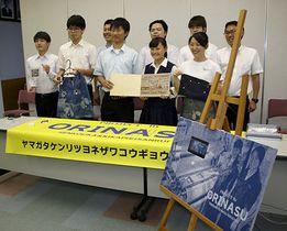 モニターを組み合わせた織物製のポスター(手前)などの作品を発表する生徒たち=米沢市・米沢工業高