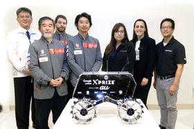 日本チーム「ハクト」(左側)と、Xプライズ財団の関係者。手前は探査車の模型=2017年11月、東京都内