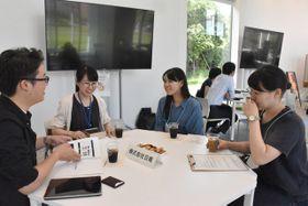 企業担当者(左と左から2人目)に、業務内容などの説明を受ける大学生たち