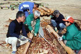 山本理事長(右端)と木材の処理に取り組む小川さん(右から2人目)たち