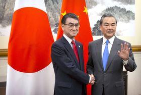 会談を前に中国の王毅国務委員兼外相(右)と握手する河野外相=15日、北京(共同)