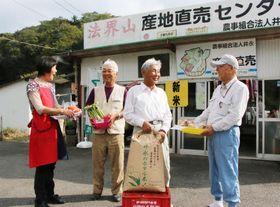 法界山産地直販センターの前で30年の歩みを振り返る田和副代表(左から2人目)と岡本代表(同3人目)たち