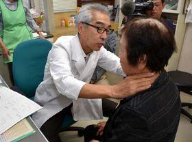 診療所で島民(手前右)を診察する岡崎副院長