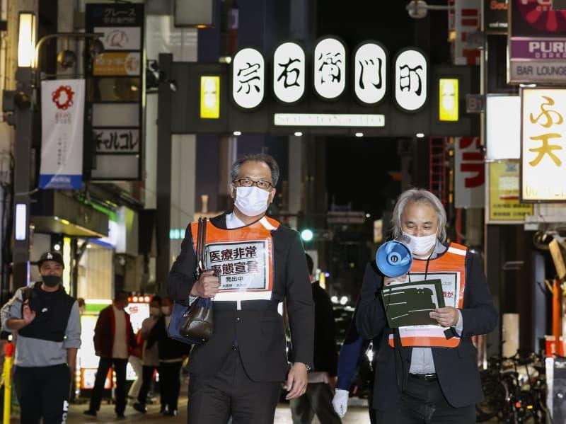 大阪・ミナミの宗右衛門町で夜間の外出自粛を求める「呼び掛け隊」=15日夜