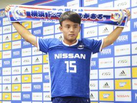 J1のFC東京から横浜Mに期限付き移籍し、ユニホームを着てポーズをとる久保建英=16日、横浜市