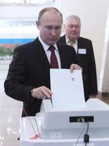 18日、モスクワ中心部の投票所で投票するプーチン大統領(タス=共同)