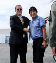 空港でメキシコのエブラルド外相(左)と握手するボリビアのモラレス大統領=12日、メキシコ市(メキシコ外務省提供・共同)