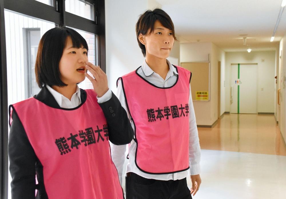 最近の被災者支援を紹介する掲示を見ながら話す佐藤りささん(左)と原田素良さん。ピンクのベストは学生ボランティアの目印=熊本学園大