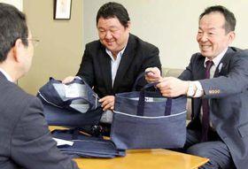 片山教育長(左)にデニム製バッグを披露する青木理事長(右)と山崎専務理事