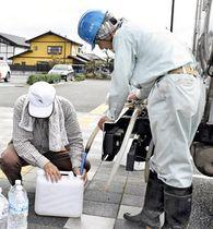 ポリタンクやペットボトルで給水を受ける市民=15日午前10時ごろ、相馬市