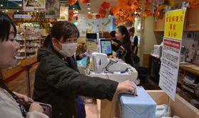 レジに設置された募金箱にお金を入れる買い物客=11日、東京・銀座わしたショップ本店