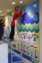 【壁画を仕上げるツペラツペラの2人=松阪市久保町の梅村幼稚園で】