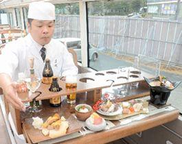バスの2階にあるテーブルに並べられた地元食材を使った料理=広島市中区、旧広島市民球場跡地
