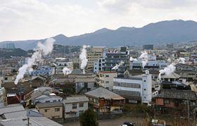温泉の湯煙が立ち上る大分県別府市の市街地=23日