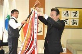 第18回大会を制した浜松市北部チームのペナントを優勝旗にくくり付ける鈴木市長(右)=浜松市役所
