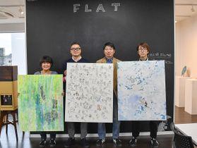 障害のあるアーティストたちの作品を手に、笑顔を見せる大平さん(左から2人目)らFLATのスタッフ=川崎市幸区