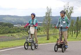 電動立ち乗り三輪車を操縦するガイド=12日、長岡市