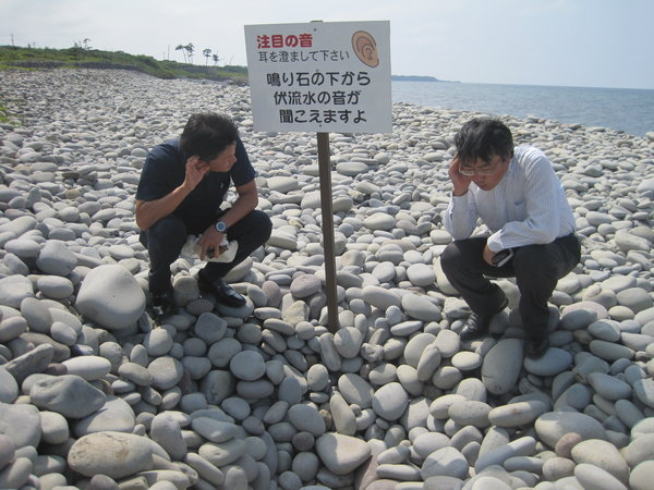 鳴り石の下から響く伏流水の音を聞く馬野さん(右)と上田さん