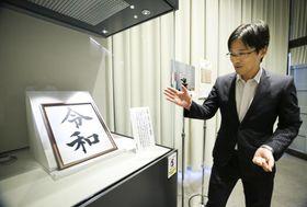 報道機関に公開された「令和」の墨書のレプリカについて説明する国立公文書館の担当者=24日午後、東京都千代田区