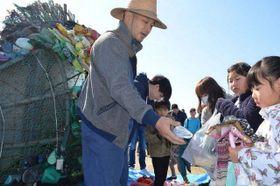 宇野コチヌの前で柴田さん(左)にごみを渡す子どもたち