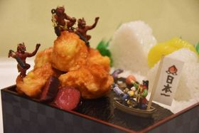 """「めざすは""""お肉が島""""」は岡山での作品展に合わせて作られた。弁当の中に桃太郎の世界を閉じ込めた"""