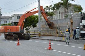 大雨の影響で傾いた住宅の擁壁=16日、沖縄市登川