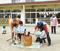 千代嵐(左)と餅つきする園児ら=木更津市高柳で 写真