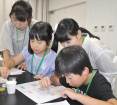 【pH試験紙を使って唾液の働きを確認する参加者ら=津市一身田上津部田の県総合博物館実習室で】