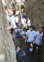 険しい岩場を登る選手(左)=熊野市紀和町湯ノ口で