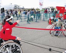 車いすテニスを選手の指導で体験する来場者