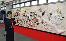 漫画家・故手塚治虫さんの人気キャラクターが描かれた大型レリーフの除幕式に出席した手塚るみ子さん=18日午前、東京都江東区