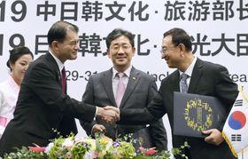 30日、韓国・仁川で開かれた日中韓文化相会合で、採択した「仁川宣言」の署名式で握手する柴山文科相(左)ら(共同)