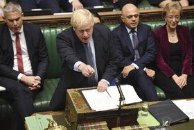 議会で発言するジョンソン首相=19日、ロンドン(AP=共同)
